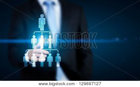 Delegate concept with businessman pointing at abstract employee hierarchy pictogram