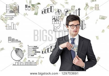 Bribery concept with intricate businessman hiding dollars in his suit pocket on business charts and diagrams background