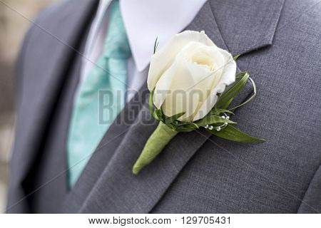 rose boutonniere for wedding or prom on a male with a blue tie
