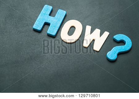 Text 'how' wording on blackboard - concept of 5 Ws and 1 H questions - colorful alphabet made from wood