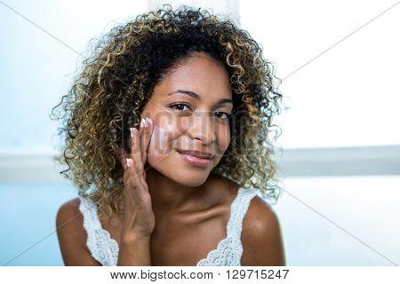 Young woman applying moisturizer in bathroom