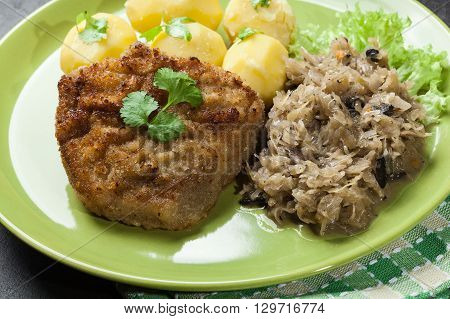 Fried Pork Schnitzel Served With Boiled Potatoes And Fried Sauer