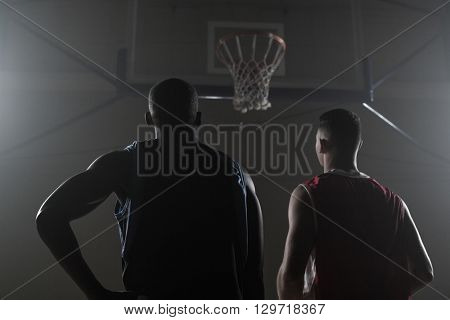 Two basketball player looking the basketball hoop in a gymnasium
