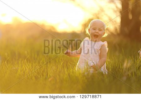 Happy Baby Girl Playing In Nature At Sunset