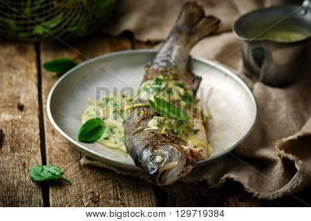 trout stewed with sauce from a sorrel. Selective focus.Style rustic