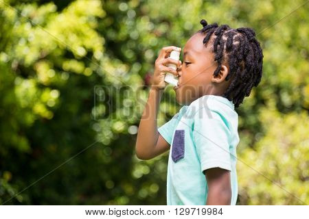 Boy using an asthma inhaler in the park