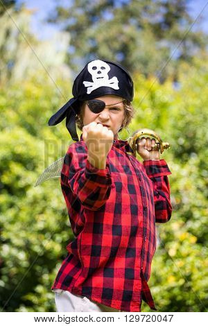 A kid with a costume of pirate is showing his strength with his fist