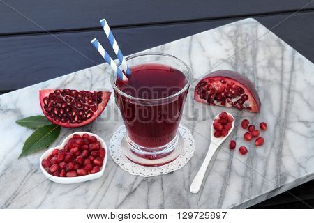 Pomegranate juice health drink with fresh fruit on marble over wooden blue background. High in vitamins, anthocyanins, and antioxidants.