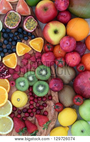 Large fresh fruit background on an olive wood board. High in antioxidants, anthocyanins, dietary fiber and vitamins.