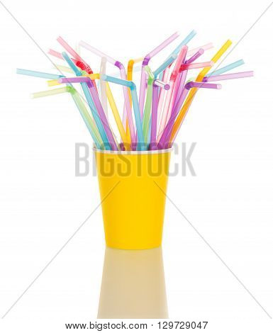 In a yellow plastic Cup colorful cocktail stick isolated on white background