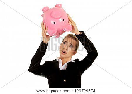Surprised businesswoman holding a piggybank