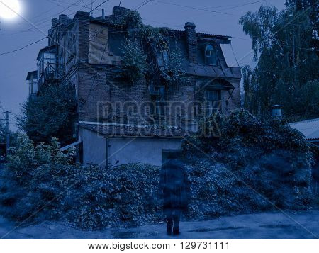 Neglected house in misty night and stranger