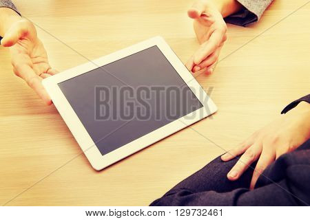 Business meeting-man showing something on tablet