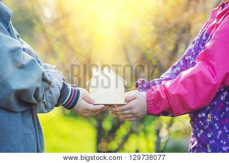 Сhildren hold little toy house in hands. Home ecology adoption happy childhood concept.