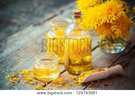 Bottles Of Dandelion Tincture Or Oil, Flower Bunch, Wooden Scoop And Honey On Table. Herbal Medicine
