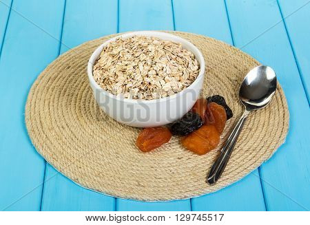 Bowl with oat flakes and dried fruit on a tree colored background in siny color.