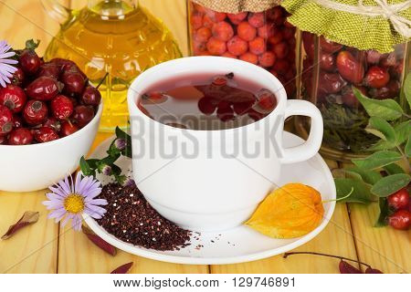 White cup with a drink from the berries of mountain ash and wild rose on a background of light wood.
