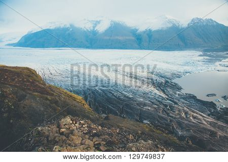 Melting of glacier in Iceland. Panorama of glacial Vatnajokull covered with volcanic ash.