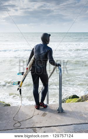 Surfer carrying surfboard on beach looking at sea