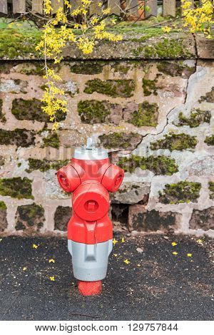 Red fire hydrant in France, against stone wall