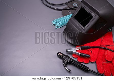 Welding equipment, welding mask, protective leather gloves, welding electrodes, high-voltage wires with clamps, cutting disc for grinder, set of accessories for arc welding. poster