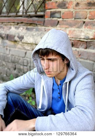 Sad Teen sit near the Brick Wall of the Old House