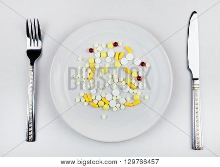 Pills in the Plate on the Table