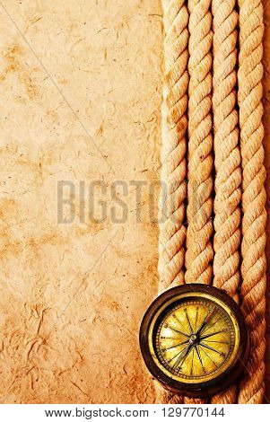Ancient Brass Compass With Rope On Vintage Old Paper Background. Retro Stale.