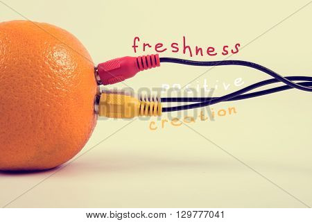 Ripe orange connected with three colored cables.