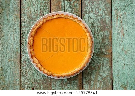 Homemade oldfashioned open round pumpkin pie on old painted wood table copyspace overhead view