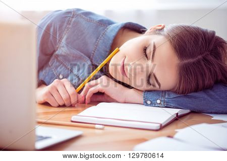 Deserve some rest. Pleasant delighted beautiful woman sitting at the table and sleeping on its surface after working in the office