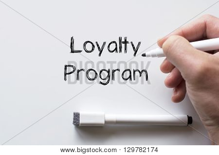 Human hand writing loyalty program on whiteboard