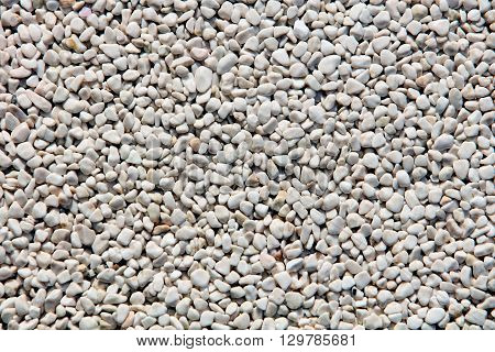 rough texture surface of exposed aggregate finish Ground stone washed floor made of small sand stone in light brown color.