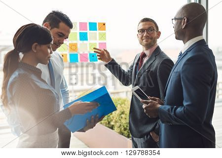 Group Of Business People With Notes On Window