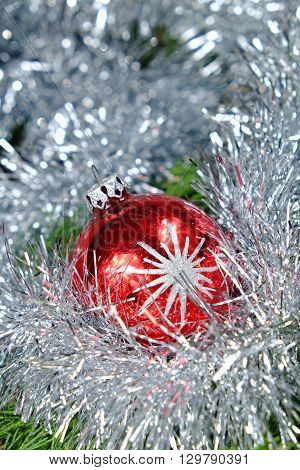 Red Christmas ball with silver stars around her christmas chain in silver color on old wooden table with green needles