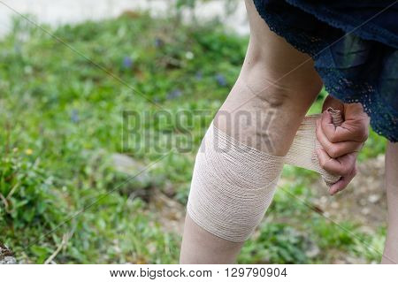 Woman with painful varicose and spider veins on her legs applying compression bandage self-helping herself. Vascular disease varicose veins problems painful unaesthetic medical condition concept. poster