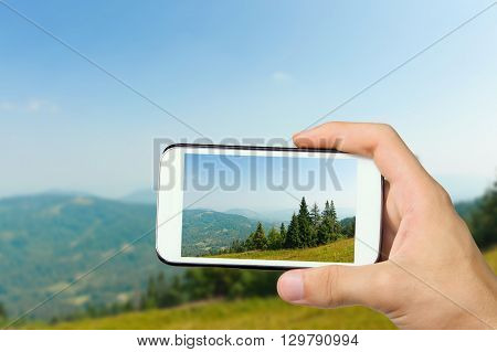 Hands taking photo a beautiful trekking path in the mountain with smartphone.
