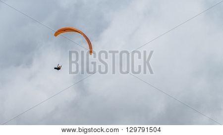 Single parachutist soar in tje cloudy sky