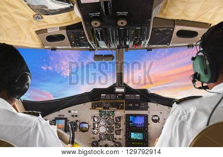 Pilots in the plane cockpit and sunset - transportation background
