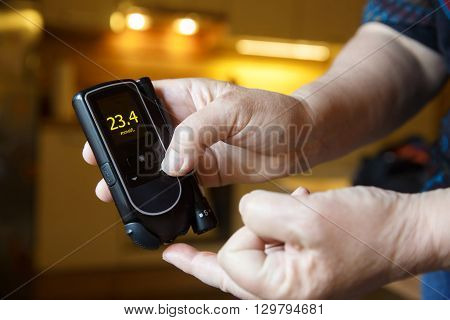 Hyperglycemic diabetic patient testing her blood for sugar level at home; high blood sugar. Medical process self-diagnose common metabolic widespread and modern epidemic disease concept.