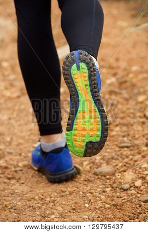 Close Up Of Woman's Sneakers Running On Dirt Road