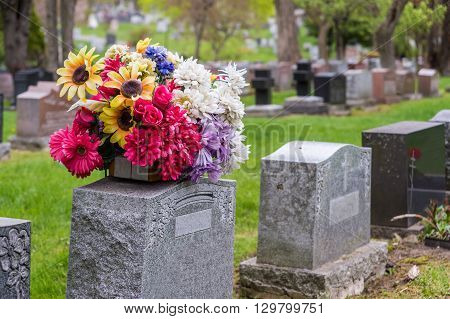 Flowers On A Tombstone In A Cemetary With Headstones In The Background