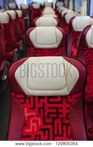 Bus seats in row with red leather, textile coating, wooden armrests and white headrests, modern comfortable tourist transport interior, selective focus