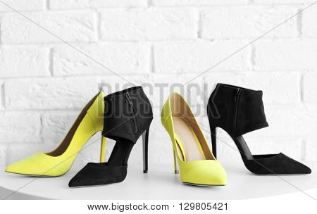 Yellow and black woman high heels on a brick wall background