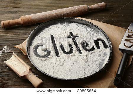 Gluten word written with flour on baking utensil over wooden table