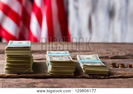 American flag, money and coins. Cash and coins near banner. Progress over the years. Citizens became richer.