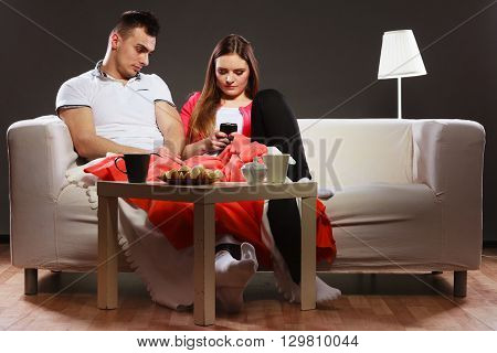 Woman Using Mobile Phone Texting And Bored Man.
