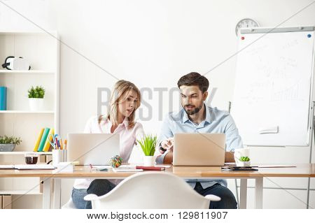 Attractive young businesswoman is explaining to colleague the concepts of work. She is pointing finger at laptop seriously. Man is sitting at desk and smiling