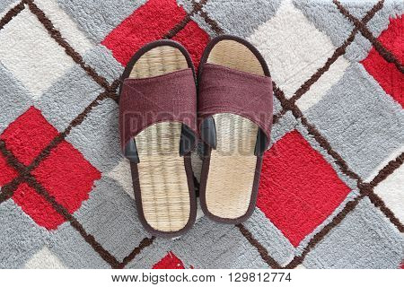 Casual shoes or Slippers for home use on the doormat background.