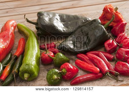 Various long short red green and black hot peppers scattered on cutting board outdoors over wooden table